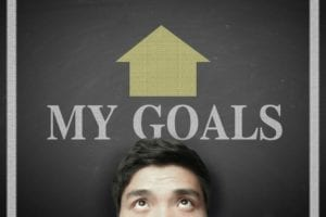 """Head of a man standing in front of a blackboard with the words """"My Goals"""" and an arrow pointing up on top of his head."""