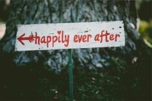 """Wooden sign with an arrow pointing to """"happily ever after."""""""
