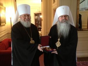 ROCOR Metropolitan Hilarion presents Metropolitan Tikhon with panagia of the Kursk Icon of the Mother of God.