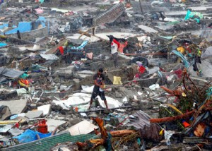 A man stands atop debris as residents salvage belongings from the ruins of their houses after Typhoon Haiyan battered Tacloban city in central Philippines November 10, 2013. The destructive force of the storm has left more than 920,000 people homeless and in desperate need of food, water, and medical attention. IOCC is working with relief partners on the ground to provide aid to residents of hard hit Tacloban and surrounding communities. CREDIT: REUTERS/Erik De Castro – Courtesy of trust.org