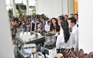 Presiden Jokowi dalam sebuah acara menikmati minum kopi bersama peserta.