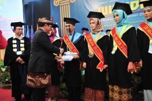 Seskab memberikan selamat kepada perwakilan wisudawan/wisudawatidi Gedung Serbaguna Graha UIGM Palembang, Sabtu (8/12). (Foto: Humas/Jay).