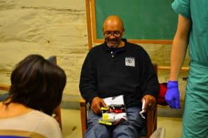 A homeless man getting new socks from The Joy of Sox at a clinic run by JeffHOPE medical students in Philly.