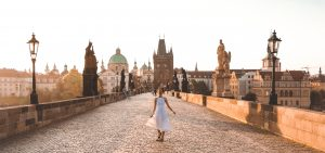 Jasmine twirling in a white dress at sunrise on the Charles Bridge, Prague