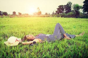 Smiling Woman Laying Down In The Grass Under A Shiny Sun