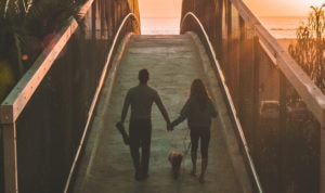 A couple walks on a bridge at sunset with their dog.