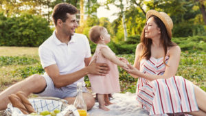 Young parents on romantic date picnic with baby