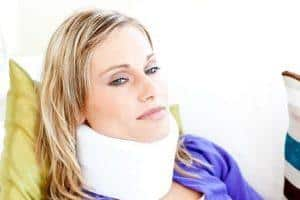 woman sitting on a sofa with a neck brace