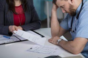 doctor in distress while reviewing paperwork