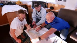 Matt, Capt. Chas, and TIm over some sailing charts