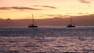 Orange sunset with two sailboats anchored in Moorea