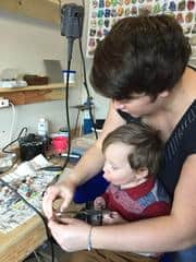 Jeana Rushton jewelry designer with her son in her studio