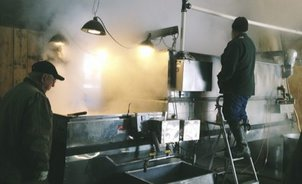 Image: two men tend to large evaporator rig, making maple syrup
