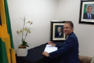 Consul General R. Oliver Mair signing the Condolence Book for former PM Edward Seaga.