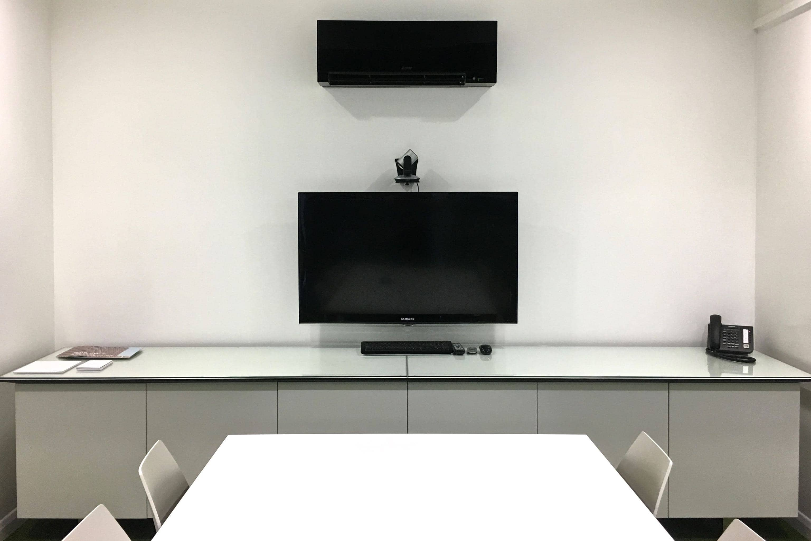 Black compact commercial air conditioning unit in white office meeting room