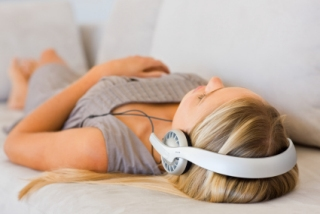 Relaxed woman lying down listening to hypnotherapy downloads