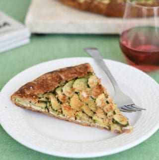 a slice of zucchini galette in a whole wheat pie crust on a plate