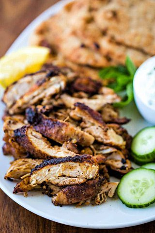 chicken shawarma on white platter with naan and cucumber slices