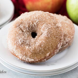Two apple cider donuts served on a small white plate.