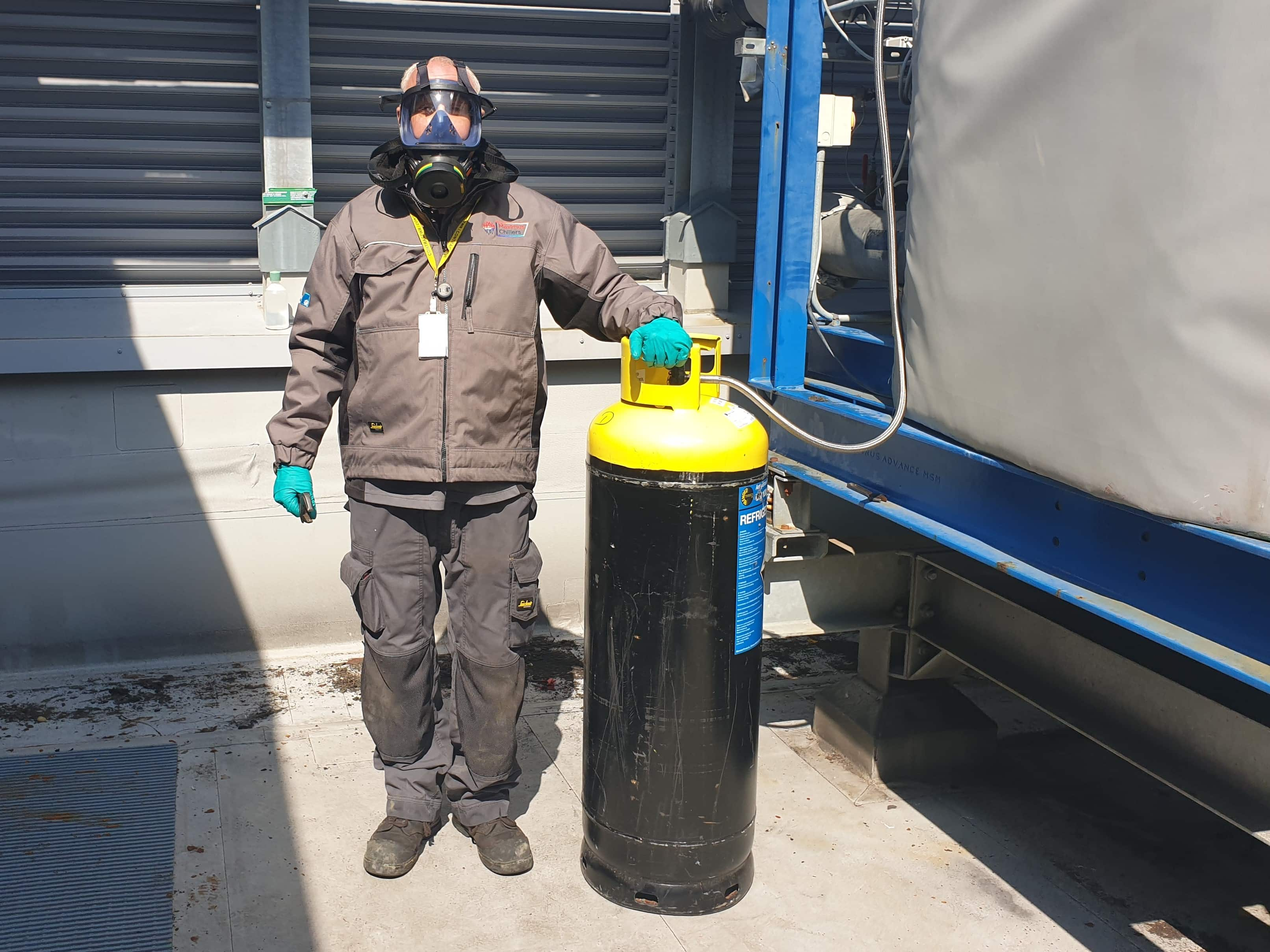Industrial refrigeration ammonia being charged by an engineer wearing breathing apparatus and gloves