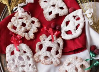 You won't believe how easy it is to make these pretty Snowflake Ornaments made out of wonton wrappers! Grab a scissors and cut pretty designs in the wrappers, fry, and dust with powdered sugar. Fun to make, delicious to eat, or to decorate a tree or mantle. | One Dish Kitchen
