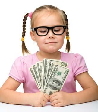 Cute cheerful little girl with paper money
