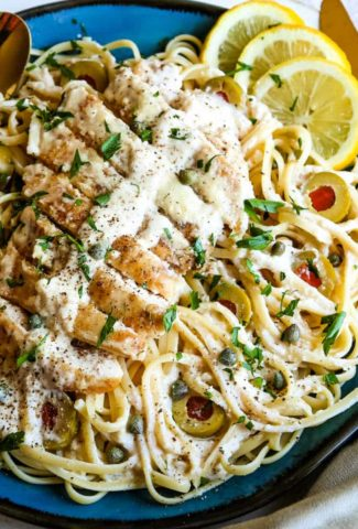 lemon chicken over pasta on a blue plate with lemon slices