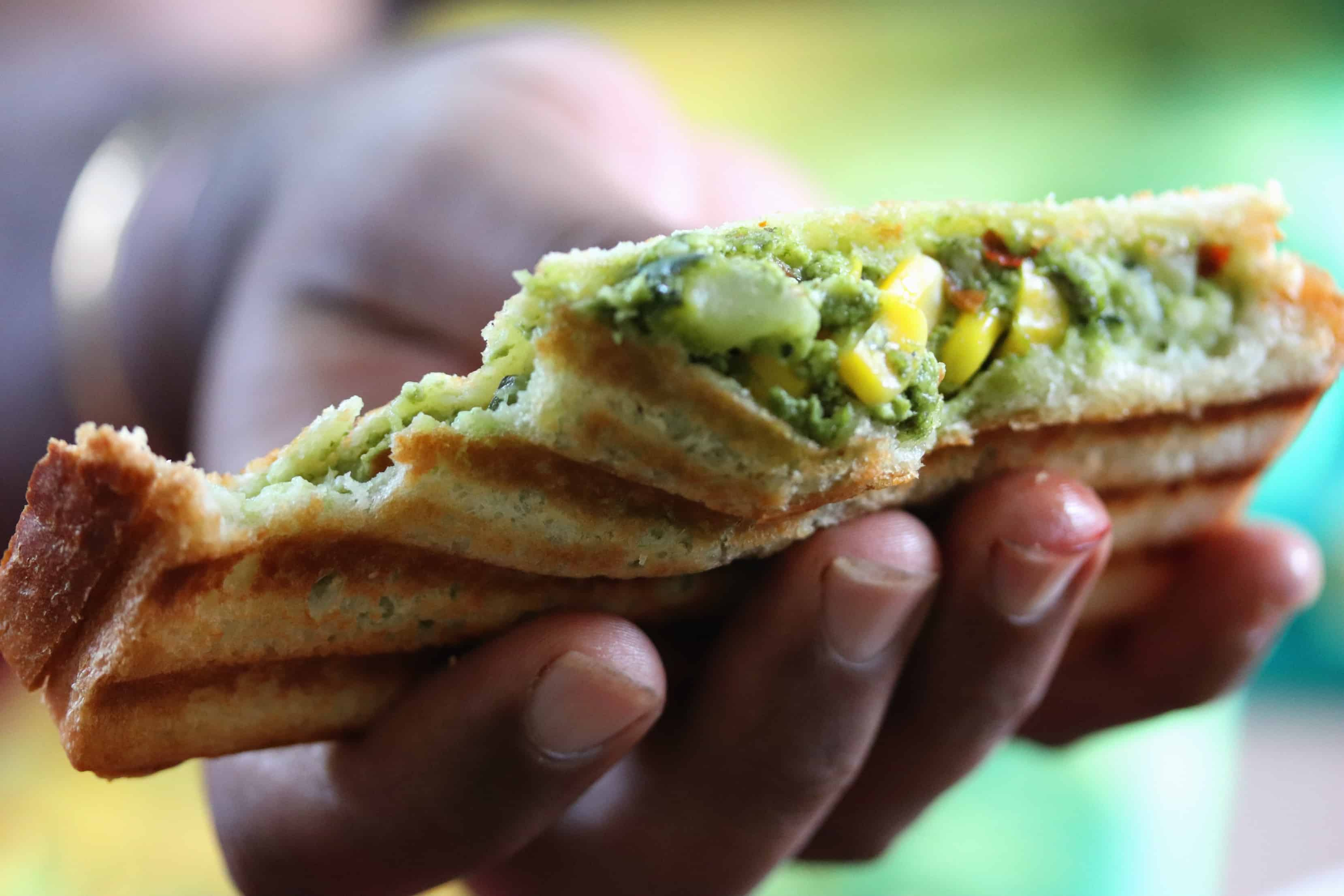 Zucchini, cottage cheese, mushroom and corn along with palak or spinach puree form the filling for this lipsmacking and filling grilled sandwich recipe. Grilled with a knob of butter or ghee, served hot with green chutney or tomato ketchup, this is a perfect recipe that can be prepared and stored in the refrigerator (the filling) a day earlier to plan the kids tiffin box the next day along or carry as a travel snack for outings or treks.