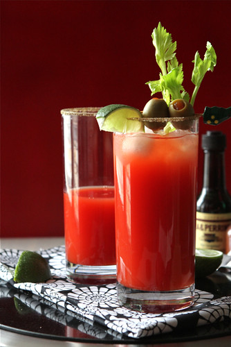 Red drink in tall glass garnished with green olives and celery
