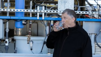 Image: Bill Gates Standing in front of the advanced technology behind the Omni Proceesor drinking water