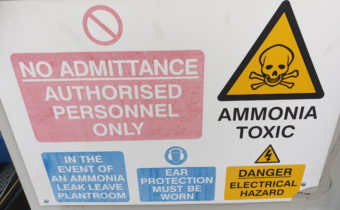 Industrial refrigeration oil change showing ammonia warning sign