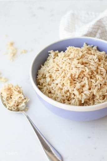 Pressure cooker brown rice in a bowl and a spoon on the tabletop