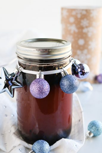 A jar of Pressure Cooker Elderberry Juice in a jar with Christmas decorations