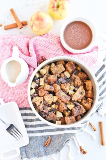 Apple Cinnamon French Toast Casserole in a white bowl with cream sauce