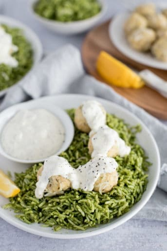 White bowl of green rice and chicken ricotta meatballs covered in a white sauce