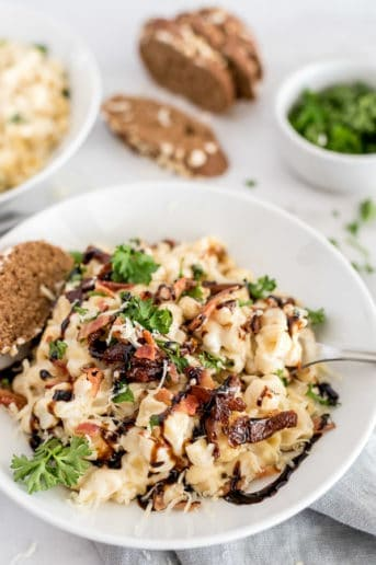 cauliflower mac and cheese in a white bowl topped with sun-dried tomatoes and balsamic glaze