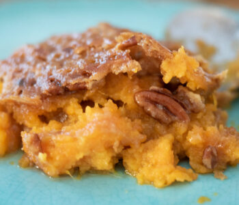 serving close up of sweet potato casserole on a blue plate
