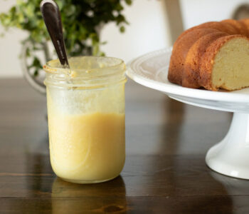 lemon curd in a jar with a pound cake in the background