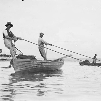 Australian fishing history - Two prawn fishermen hauling prawning nets from their boat, NSW ca 1930