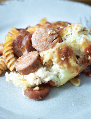 close up of baked sausage pasta on a grey plate