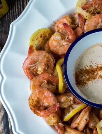 old bay spiced shrimp with dip in large bowl next to lemon and box of old bay
