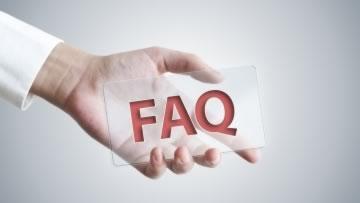 Eine Hand hält ein Schild mit der Aufschrift FAQ.