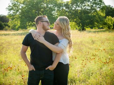 engagement photos of a man in a black shirt wearing glasses and a female blonde in a white shirt and jeans standing in a field during sunset