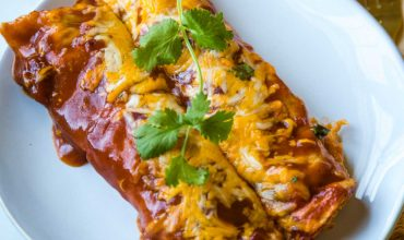 chicken enchiladas with red sauce and cheese on a white plate