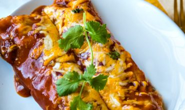 two chicken enchiladas with cheese and red sauce garnished with cilantro on a white plate