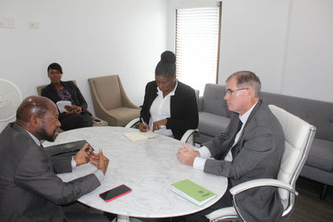 St Kitts and Nevis' Leader of the Opposition, the Right Hon Dr Denzil L. Douglas (left), Mrs Amelia Swift (center at the table) and Mr Mike Pennell