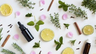 Essential oil bottle among herbs and fruit