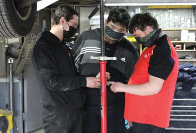 As part of vocational education, Green Chimneys School students are working at local businesses. This image shows 3 individuals under a car at Brewster Shell, two of whom are Green Chimneys students.