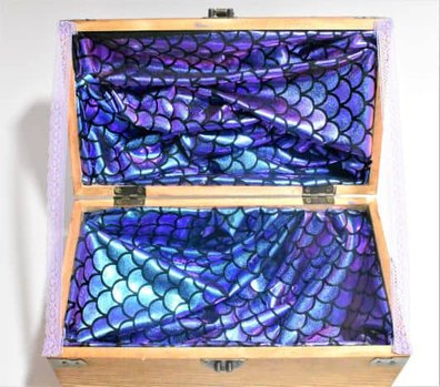 lace holding up mermaid party centerpiece treasure chest lid