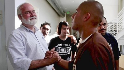 Image: Young man shakes Father Greg Boyle's hand